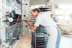 Baker woman getting bread out of bakery oven stock photo