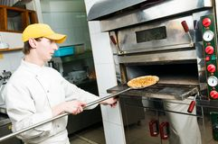 Baker at work. One chef baker in white uniform baking a pizza bread in oven at commercial kitchen Stock Photo