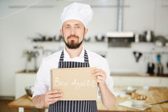 Baker at work. Professional baker holding notepad with wish of good appetite Stock Photos