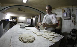 Baker at work. A baker works on the dough for cakes and pastry in a bakery downtown Palma, in the spanish island of mallorca Stock Photos