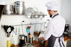 Baker working. Busy baker cooking tasty food at workplace Stock Image