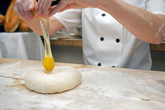 Baker working with dough. Baker working with fresh dough on baker's table Stock Photography