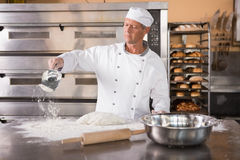 Baker working with scoop and dough. In the kitchen of the bakery Stock Photos