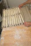 Baker working with uncooked dough forming it into long rolls Royalty Free Stock Photo
