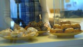 Baker zet broodjes op de teller stock footage