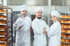 Bakers on the background of trays with breads in a bakery. Smiling bakers on the background of trays with breads in a bakery factory royalty free stock photos