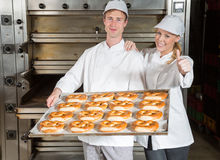 Bakers with baking tray in bakery showing thumbs up stock photos
