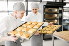 Bakers with buns at the bakery. Two handsome bakers standing with tray full of freshly baked buns at the manufacturing royalty free stock photography