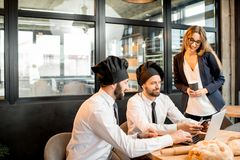 Bakers with businesswoman in the cafe. Businesswoman with two elegant bakers or chef cooks working with laptop in the cafe with kitchen on the background royalty free stock photo