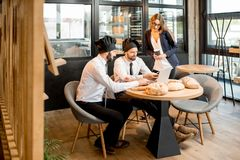 Bakers with businesswoman in the cafe. Businesswoman with two elegant bakers or chef cooks working with laptop in the cafe with kitchen on the background stock image