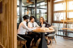 Bakers with businesswoman in the cafe. Businesswoman with two elegant bakers or chef cooks working with laptop in the cafe with kitchen on the background stock photos