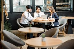 Bakers with businesswoman in the cafe. Businesswoman with two elegant bakers or chef cooks working with laptop in the cafe with kitchen on the background royalty free stock photos