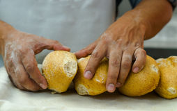Bakers hands stacking fresh delicious buns of bread against each other Royalty Free Stock Photography