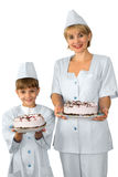 Bakers with iced cakes. Female baker in uniform with a young boy assistant both smiling and holding iced cakes with chocolate decoration Stock Photo