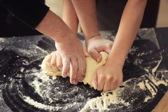 Bakers kneading dough on kitchen table royalty free stock photography