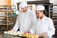 Bakers looking at trays of dough and pastry Stock Photo