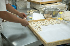 Bakers making Fresh Pretzels on Dough Covered Table Royalty Free Stock Photo