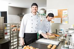 Bakers Preparing Tasty Pastries In Bakery. Hispanic male chefs preparing choux puffs in professional kitchen stock images