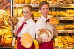 Bakers presenting loafs of bread in a bakery. Two bakers or shopkeepers in a bakery presenting different types of bread royalty free stock photo