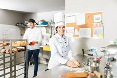 Bakers Smiling In Commercial Kitchen. Confident young baker in uniform preparing dough for bread in restaurant kitchen royalty free stock photo