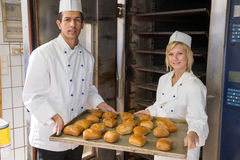 Bakers with tablet of bread in bakery or bakehouse. Two bakers with tablet of buns in a bakery Royalty Free Stock Photo