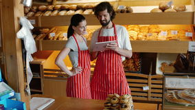 Bakers using digital tablet. In the bakery shop 4k stock video footage