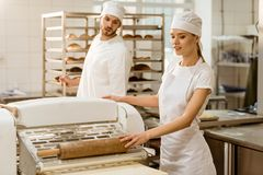 Bakers using industrial dough roller. At baking manufacture stock images