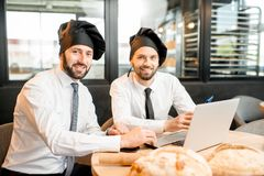 Bakers working with laptop in the office. Portrait of two elegant bakers in white shirts and caps working with laptop in the bakery office Royalty Free Stock Image