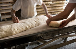 Bakers working on large loaf of bread Stock Image