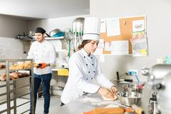 Bakers Working Together In Bakery Kitchen. Female chef kneading dough while colleague removing fresh bread from rack in kitchen royalty free stock photo