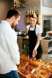 bakersfield Деятельность женщины, продавая хлебопекарню к мужчине стоковое изображение