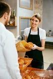 bakersfield Деятельность женщины, продавая хлебопекарню к мужчине стоковая фотография