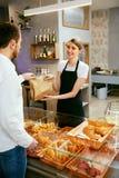 bakersfield Деятельность женщины, продавая хлебопекарню к мужчине стоковая фотография rf