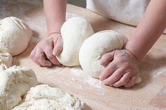 Bakery. Woman hands at work mixing dough on the counter royalty free stock image