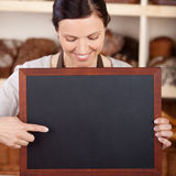 Bakery assistant pointing to a blank blackboard Stock Image