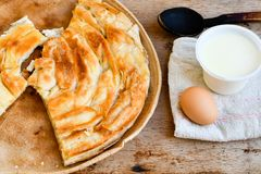 Bakery background – cheese pie. Bakery background – home made cheese pie with bio egg, yogurt and wooden spoon on wooden board stock images