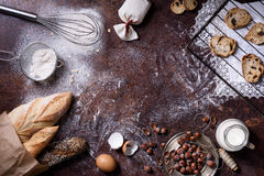 Bakery background, baking ingredients over rustic kitchen countertop. Baked cookies with hazelnuts, rye bread, milk and eggs. Top view, copy space Royalty Free Stock Photos