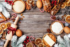 Bakery background with ingredients for cooking christmas baking decorated with fir tree. Flour, brown sugar, eggs and spices. stock image