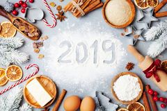 Bakery background with ingredients for cooking decorated with fir tree and new year 2019. Flour, brown sugar, eggs and spices. royalty free stock photography