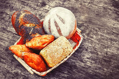 Bakery bread and rolls on old wooden table in wicker basket. The concept of food advertising. stock image