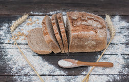Bakery Bread on a Wooden Table. Rustic bread, flour and wheat on vintage wood table Stock Images