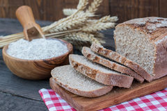 Bakery Bread on a Wooden Table. Rustic cut bread, flour on Wooden bowl, wheat and cutting board and picnic cloth on vintage wood table Royalty Free Stock Photography