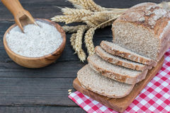 Bakery Bread on a Wooden Table. Rustic cut bread, flour on Wooden bowl, wheat and cutting board and picnic cloth on vintage wood table Royalty Free Stock Photo