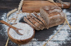 Bakery Bread on a Wooden Table. Rustic cut bread, flour on Wooden bowl, wheat and cutting board on vintage wood table Royalty Free Stock Photography
