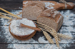Bakery Bread on a Wooden Table. Rustic cut bread, flour on Wooden bowl, wheat and cutting board on vintage wood table Royalty Free Stock Image
