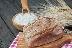 Bakery Bread on a Wooden Table. Rustic  bread, flour on Wooden bowl, wheat and cutting board and picnic cloth on vintage wood table Stock Photography