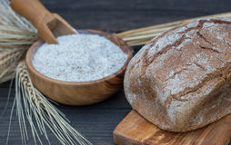Bakery Bread on a Wooden Table. Rustic  bread, flour on Wooden bowl, wheat and cutting board on vintage wood table Royalty Free Stock Images