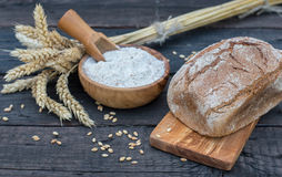 Bakery Bread on a Wooden Table. Rustic bread, flour on Wooden bowl, wheat and cutting board on vintage wood table Royalty Free Stock Image