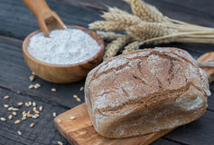 Bakery Bread on a Wooden Table. Rustic bread, flour on Wooden bowl, wheat and cutting board on vintage wood table Royalty Free Stock Photo