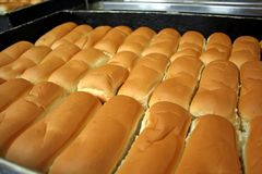 Bakery buns. Rows of bread loaves in racks in a bakery Royalty Free Stock Image